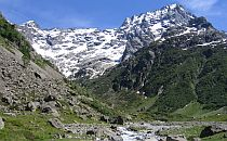 Alpine landscape in France. High snowcapped mountains in the background. Rocky terrain interspersed with green vegetation in the foreground