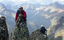 Two climbers high on a peak in the Alps