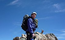 Person in mountaineering gear almost at the top of an alpine summit. Bright weather and deep blue sky