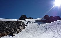 Group of climbers walking up a snow-covered slope, while a bright sun shines down from a deep blue sky