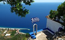 Looking down a steep drop from a high viewpoint past a Greek flag blowing in the wind towards a coastal village and marina in front of a dark blue sea