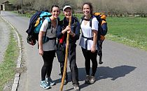 Three women hiking with backpacks and a heavy stick