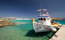 Small boat anchored in a harbor in turquoise water under a clear blue sky