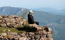 Hiker sitting on an ancient stone wall, looking at the hills in the distance