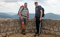 Two walkers posing for a photo infront of an ancient stone wall