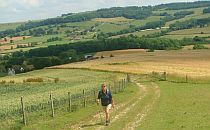 Hiker walking on a trail uphill a meadow in England