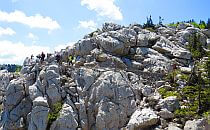 People walking on a trail along a rocky hill