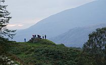 People staing on a rocky hill, great mointains in the background, a walking path in front