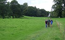People walking a trail on a nice green field in English Lake District
