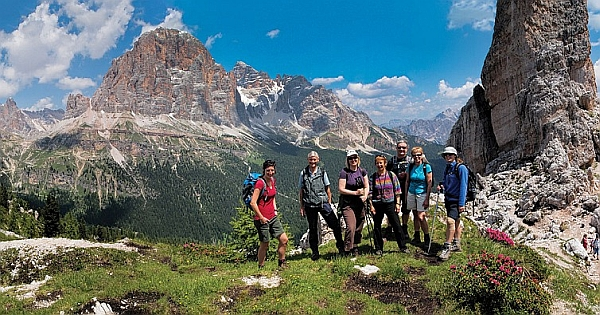 Walkers posing for a photo on a green patch during their walking holiday in the Italian Dolomites, beautiful rock mountains in the background