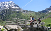 Group of people taking a break at a bridge during a walk in the French Alps