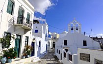 Street in a small village in Greece. Whitewashed houses under a blue sky.
