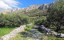 Stone hiking path going up towards a range of cliffs