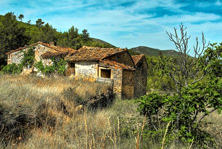 An old house in a rural, hilly landscape