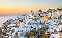 Whitewahsed houses on a hill on Santorini overlooking the sea in golden light