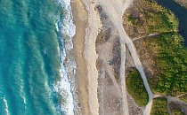 Photo of turquoise sea and golden beach with sandy paths taken from above