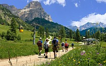 People walking on a path in the Italian Dolomites, cabin lift on the side