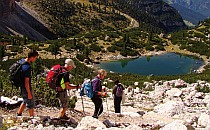 Hikers walking down some rocks to a crystal clear lake