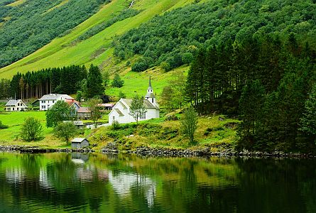 green hills with pine forest and small church and houses in Norway