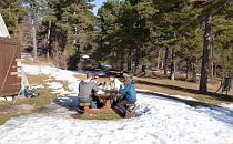 Group of people outdoors in the snow having lunch at a wooden table
