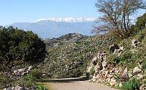 A deserted mountain road in Crete - high mountains with snow on top in the distance - clear blue sky