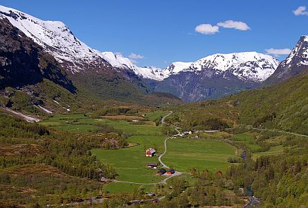 green wide valley with scattered houses and steep mountains with snow caps