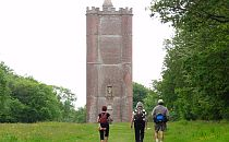 group of people on walking holiday approaching a tower