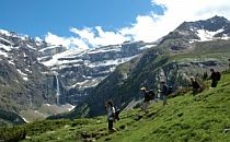 People walking down a mountain track in the French Pyrenees. A wide mountainous landscape with snowcapped mountains, a blue sky and a high waterfall in the distance
