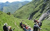 Group of walkers with a guide resting at the side of a narrow mountain path