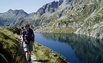 People walking on a track past a quietly flowing river. Mountains are reflected in the water