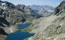 Looking down from a high viewpoint towards a deep blue lake. The lake is surrounded by grey mountains underneath a blue sky.
