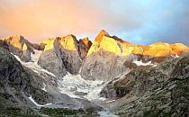The sunset illuminates the top of a group of mountains in the French Pyrenees