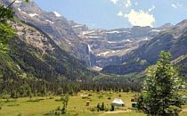 High mountains surround a green meadow in the French Pyrenees