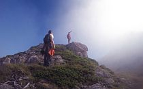 Hikers on a high rock in the Pyrenees, reaching for the sun