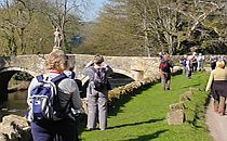 rambling club group walking towards a medieval bridge in somerset