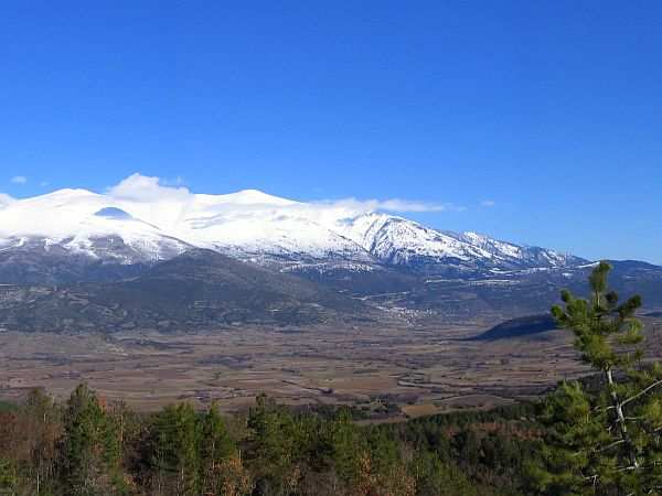Mount Olympus with snow at the peaks and a broad valley in front
