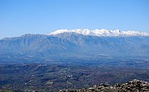 Panoramic view across wide landscape on crete with snowcapped mountains in the distance