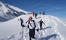 Group of climbers with a guide walking past a lake towards high snow-capped mountains in the background.