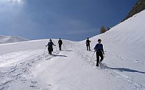 Walkers climbing up a steep alpine slope