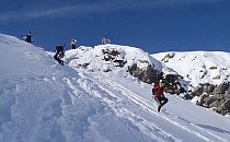 Person in mountaineering gear almost at the top of an alpine summit. Bright weather and dep blue sky.