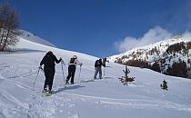 Group of climbers walking up a snow-covered slope, while a bright sun shines down from a deep blue sky.