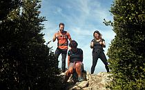 Three walkers on the top of a rocky hill