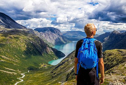 wide panoramic view on Norwegian fjords and mountains with a walker with blue backpack