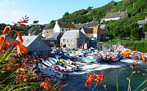 A small fishing village with small boats in a picturesque cove in Cornwall