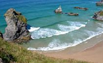 View from the cliffs down unto the clear blue sea and a sandy beach in Cornwall.