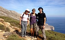 Three hikers in front of the sea