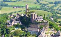 Aerial view onto a Dordogne castle on a hilltop, surrounded by green farm-fields