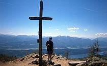 Walker next to a wooden cross on a mountain top