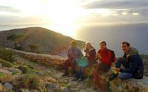 Small group of walkers resting on a low stone wall looking out over the Aegean Sea.