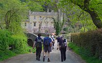 Group of people on a walking holiday in Somerset, approaching a castle